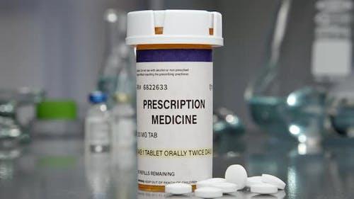 Prescription medicine bottle and pills in medical lab