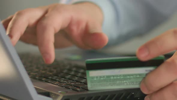 Cover Image for Businessperson Typing Bank Card Number on Laptop, Close-Up of Man's Fingers
