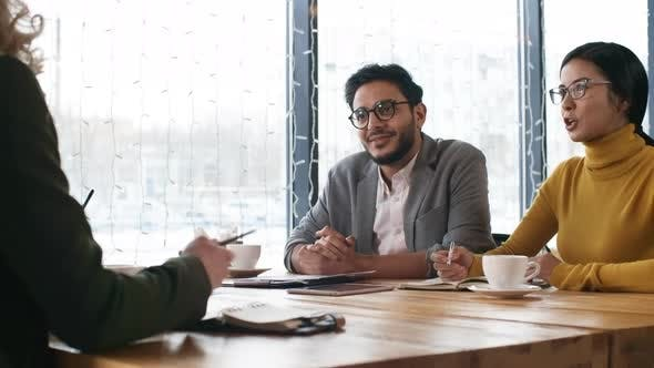 Thumbnail for Multiethnic Colleagues Smiling and Talking with Business Partners on Lunch