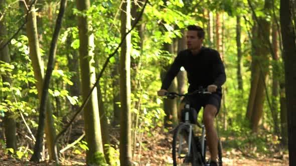 Thumbnail for A Cyclist Rides Down a Path Through a Forest