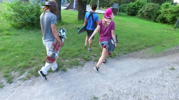 Group of three skateboarders going to skatepark