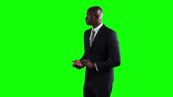 Thumbnail for an African American man in suit using a phone in green background