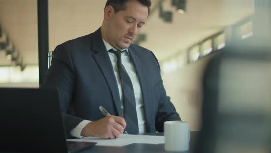 Thumbnail for A businessman consulting with his partner before signing a contract during a business meting