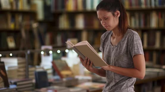 Beautiful young woman reading in library by bookstacks