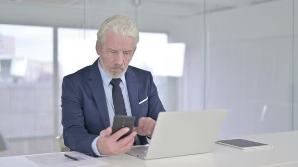 Happy Old Businessman Talking on Smartphone in Office