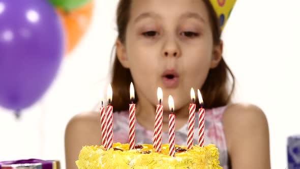 Thumbnail for Geburtstagskuchen bläst Kerzen auf einem Geburtstagskuchen aus. Im Hintergrund, Bälle. Zeitlupe