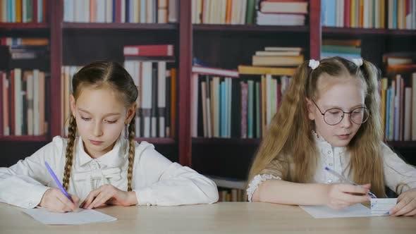 Focused Schoolgirls Writing Exam and Cheating in Classroom