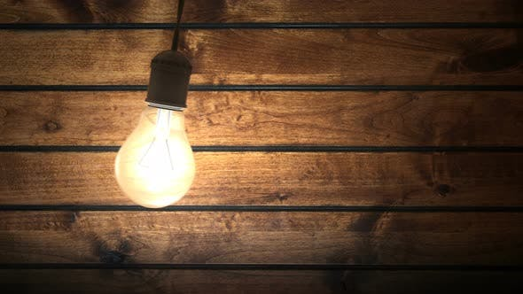 Swinging Incandescent Bulb in Timber House Darkened Room