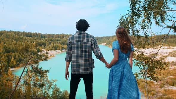 Young Happy Couple Holding Hands and Looking on a Landscape of Blue Lake and Forest