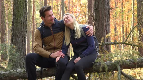 Thumbnail for A Hiking Couple Sits on a Broken Tree, Hugs and Talks