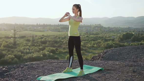 Cover Image for Athletic Girl is Doing Physical Exercise in a Top of Mountain Over the River in Summer