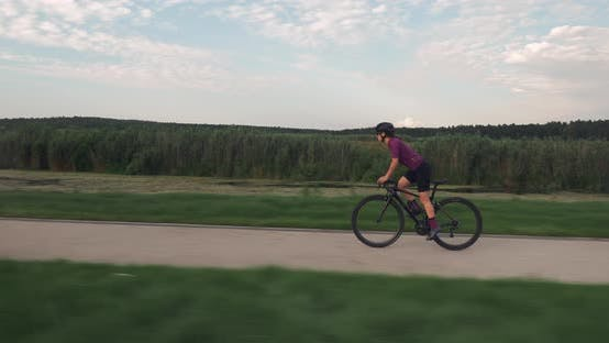 Thumbnail for Fit female athlete is pedaling hard out of saddle on road bike. Triathlete rides a bike.