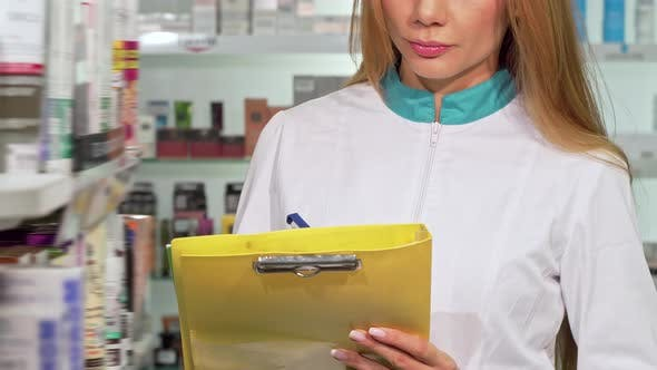 Thumbnail for Unrecognizable Female Pharmacist Writing on Clipboard at Drugstore