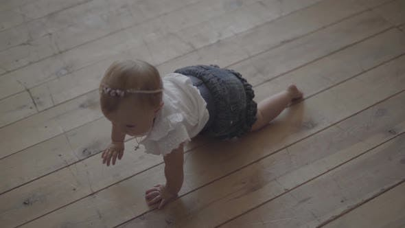 Thumbnail for Adorable Baby Girl Crawls on the Floor of the House. Kid Playing at Home. Adorable Happy Child
