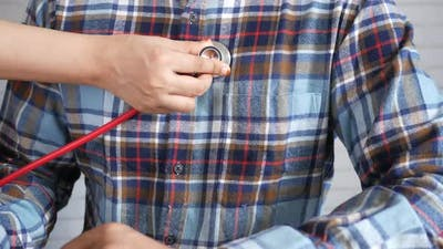 Doctor Using a Stethoscope Checking Body Close Up