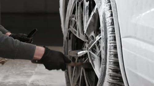 Hands of Young Man Holding Special Cleaning Brush Washing Car Wheel with Foam