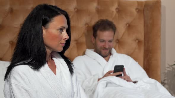 Thumbnail for Mature Woman Looking Unhappy While Her Husband Texting on Smart Phone