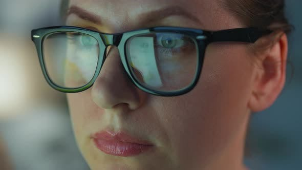 Woman in Glasses Looking on the Monitor and and Working with Charts and Analytics