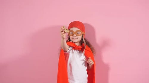 Awesome Girl Child Wearing Red Cloak and Helmet of Pilot Raised Hands Up Holding Wooden Toy Plane