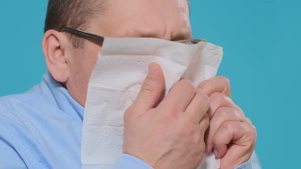 Thumbnail for Man Sneezes Into White Paper Napkin