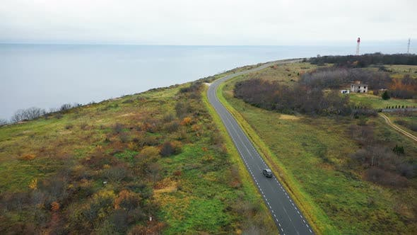 Cover Image for Drone Flying Above Black Car Moving Along Clear Road Near Beautiful Lighthouse Sea Bay and Autumn
