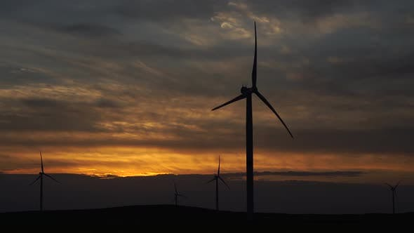 Motion the Blades of a Large Wind Turbine in a Field Against a Background of Orange Sunset on the