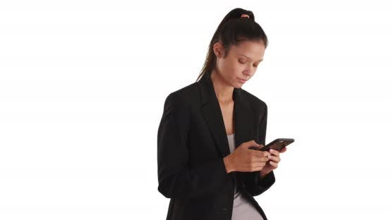 Pretty business woman wearing blazer texting with mobile phone in studio