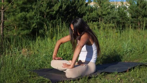 Brunette Woman Doing Asana with a Vacuum in Nature