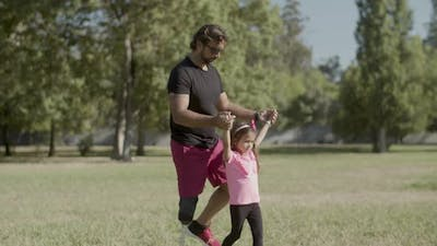 Tracking Shot of Handicapped Dad Lifting Daughter By Hands