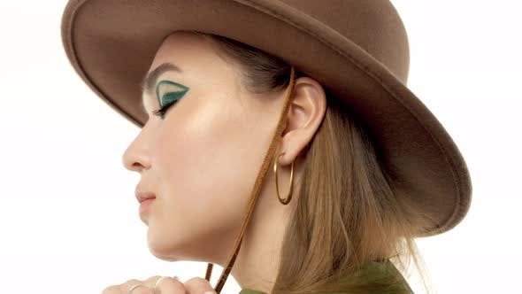 Thumbnail for Woman in a Autumn Look in Studio in Green Parka and Hat Turns and Poses To the Camera