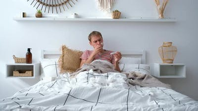 Man Lying in Bed with High Fever and a Flu