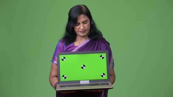 Thumbnail for Mature Beautiful Indian Woman As Call Center Representative Showing Laptop
