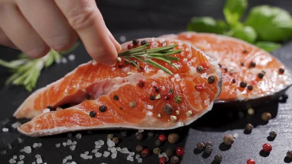 Thumbnail for Salmon. Raw Trout Red Fish Steak with Herbs and Lemon and Olive Oil Rotated on Slate.