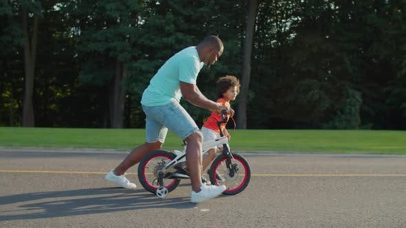 Thumbnail for Mischievous Father Riding Kids Bicycle in Park