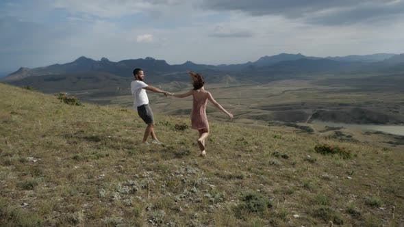 Thumbnail for The Happy Couple Holding Hands, Running Along a Plain Under the Overcast Sky