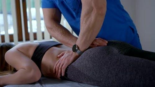 Eine Frau erhält eine Prozedur im Büro eines Osteopathen zur Behandlung der Rückenbeweglichkeit