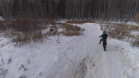 Aerial view of Racer motorcycle rides on motocross snowy track in winter 04