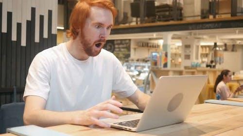 Shocked, Wondering Redhead Beard Man Working on Laptop