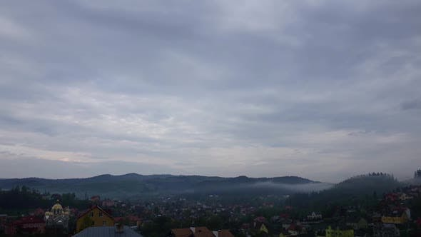 Thumbnail for Rainy Gray Spring Clouds Over Small Town in Mountains, Timelapse