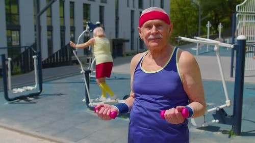 Senior Man Grandfather Doing Active Training Weightlifting Exercising with Dumbbell on Playground