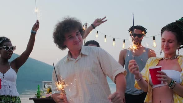 Excited Friends Dancing with Sparklers at Lake Party