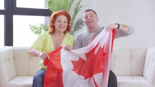 Happy Couple of Immigrants Holding Canadian Flag Singing Anthem Sitting on Couch in Living Room
