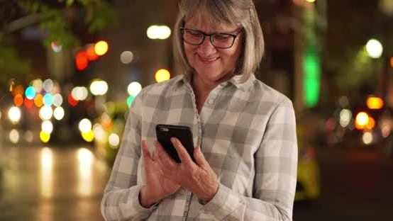 Thumbnail for Happy senior person texting friend on cellphone outside in city street at night