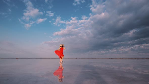 Thumbnail for Woman Tourist in a Waving Dress Walks Along a Salt Lake in Which the Sky Is Reflected