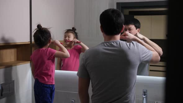 Cover Image for Asian Dad and Daughter Brushing Teeth in Bathroom