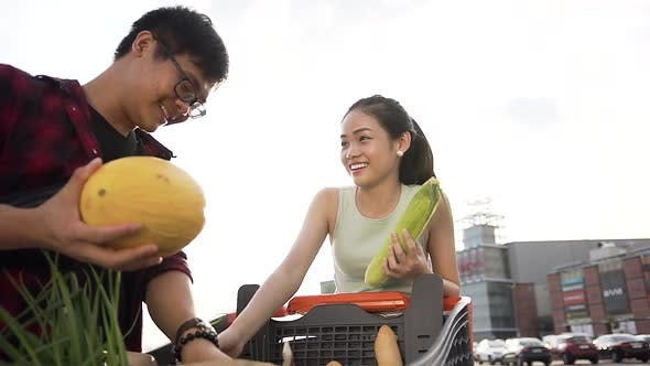 Thumbnail for Asian Couple Puts into Packets Purchased Food from the Shopping Trolley