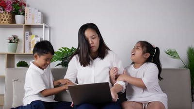 Mother trying work on laptop computer and disturbed by children.