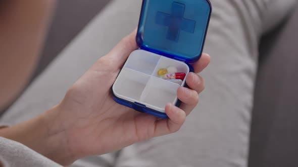 Thumbnail for Frau legt Pillen in eine Pillendose