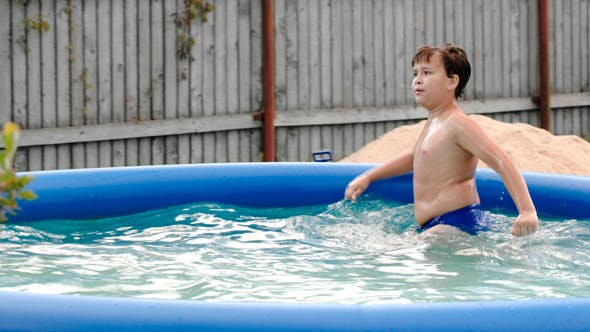 Thumbnail for Boy Swimming In Inflatable Pool In The Yard