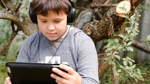 Thumbnail for Boy In Headphones With Touchpad Outdoor